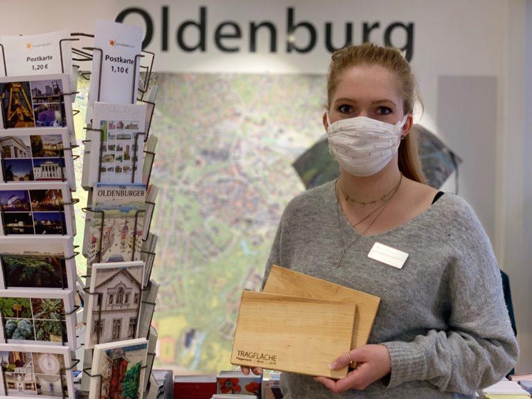 Auszubildende in der Oldenburg-Info im Lappan mit zwei Fliegerhorst-Schneidebrettern.